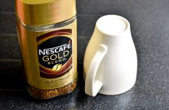 Nescafe Gold Blend instant coffee and cup. A jar of Nescafe gold blend coffee with an upturned cup ready for making a hot drink Stock Image