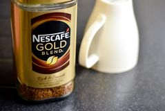 Nescafe Gold Blend instant coffee and cup. A jar of Nescafe gold blend coffee with an upturned cup ready for making a hot drink Royalty Free Stock Images