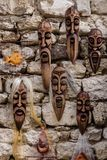 Nesebar, Bulgaria-08.15.2018: Carved bulgarian wooden masks of different perfumes on wall in the street market. Decorated stock images