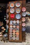 Nesebar, Bulgaria-08 15 2018: Placas e pratos cerâmicos búlgaros tradicionais na parede no mercado de rua Modelos coloridos da ar foto de stock
