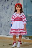 Nesebr,保加利亚- 2013年6月13日, :有花的小深色头发的女孩在她的头在一套全国舞蹈服装站立 库存照片