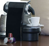 Nespresso capsules and coffee machine. With a cup of coffee Royalty Free Stock Images