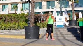 NESSEBAR, БОЛГАРИЯ - 1-ОЕ СЕНТЯБРЯ 2016: Неопознанная взрослая атлетическая женщина протягивая перед ее бегом видеоматериал