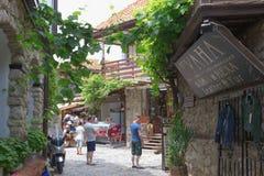 NESSEBAR BULGARIEN, JUNY 18, 2016: turistbesök som souvenir shoppar i gatorna av den gamla staden av Nessebar Royaltyfri Bild