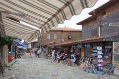 NESSEBAR BULGARIEN, JUNY 18, 2016: turistbesök som souvenir shoppar i gatorna av den gamla staden av Nessebar Royaltyfria Foton