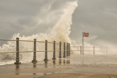 Nessun segno di bagno come onde della tempesta dell'alto mare si rompe sopra il braccio del porto Immagini Stock