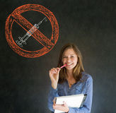 Nessuna mano sorridente della penna e della carta della donna delle droghe sul mento sul fondo della lavagna Fotografie Stock