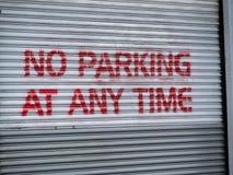 Nessuno spruzzo di parcheggio in qualunque momento ha dipinto il segnale di pericolo sulla porta del garage fotografia stock libera da diritti