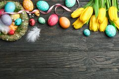 Nest with сolorful easter eggs, flowers and feathers on wooden background. Festive tradition. Space for text. Top view stock images