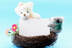 Nest with a blank card and toy teddy bear Royalty Free Stock Image