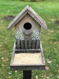 A nest box or bird house decorated with white flowers. A nest box, also spelled nestbox, is a man-made enclosure provided for animals to nest in. Nest boxes are Stock Photo