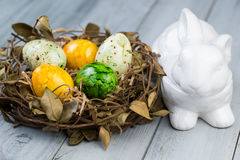 Nest with colored Easter eggs and ceramic rabbit box. On wooden background Royalty Free Stock Photo