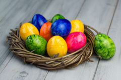 Nest with colored Easter eggs on a wooden background. Nest with multi colored Easter eggs on a wooden background Royalty Free Stock Photography