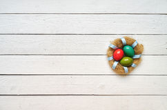 Nest colored eggs wreath on white wooden planks background stock photos