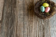 Nest with colorful eggs on aged wood royalty free stock images