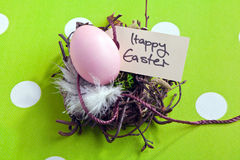 Nest With Easter Egg. Colored egg in a small nest with a Happy Easter tag Stock Photo