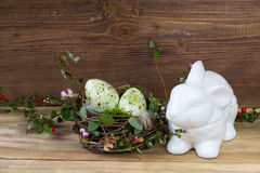 Nest with Easter eggs and ceramic rabbit box on wooden background Royalty Free Stock Image