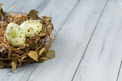 Nest with Easter eggs on a wooden background Stock Photo
