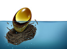 Nest Egg Crisis. Financial concept as a golden oval and nesting bird twigs falling into water as a metaphor of finance debt trouble and savings loss due to bad Royalty Free Stock Photography