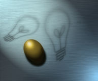 Nest Egg Ideas. Ideas represented by shadows and a golden egg represents wealth Stock Image
