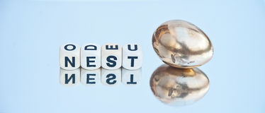 Nest egg. Text ' nest ' in uppercase letters on small white cubes next to a golden egg, concept image of savings towards a nest egg isolated on a bright royalty free stock images