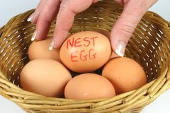 Nest Eggs. Hand placing 'nest' eggs in one basket Royalty Free Stock Photography