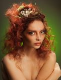 Nest with eggs in woman's hair. Beauty portrait of a red curly hair woman with birds nest with eggs in her hairstyle Stock Image