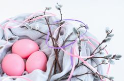 Nest of fabric with pink Easter eggs decorated with silk ribbons and pussy willow on white. royalty free stock image