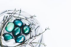 Nest of fabric with turquoise colored Easter eggs decorated with pussy willow on white. Copy space. royalty free stock photography
