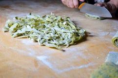Nest of fresh nettle noodles on cutting borad Stock Photos