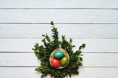 Nest gekleurde eierenkroon op witte houten plankenachtergrond Stock Foto's