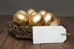 Nest with golden eggs with a tag and place for text on a wooden background. The concept of successful retirement.  Royalty Free Stock Photo