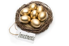 Nest with golden eggs with a tag and a word of investments on a white background. The concept of successful retirement.  Stock Photo