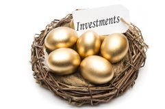 Nest with golden eggs with a tag and a word of investments on a white background. The concept of successful retirement.  Stock Photography