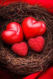 Nest with hearts. Little cozy nest with four red hearts. Family concept - attachment parenting. Parents and children Royalty Free Stock Image
