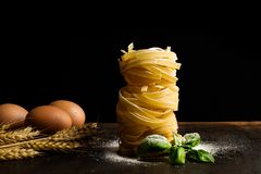 Nest noodles with basil leaves, brown eggs and flour. On a dark background stock photos