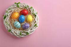Nest with painted Easter eggs and space for text on color background. Top view royalty free stock photography
