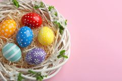Nest with painted Easter eggs and space for text on color background. Top view stock photography