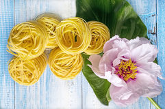 Nest pasta on a blue wooden background next to a large beautiful pink peony flower. Horizontal background. Stock Photos