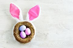 A nest with three white Easter eggs and bunny ears at home on Easter day Royalty Free Stock Photo