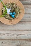 Nest in a wicker hat and painted spotted Easter eggs with flower. In the top left corner. Empty text space royalty free stock photos