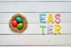Nest wreath, eggs, easter folded paper origami colorful lettering on white wooden planks rustic background Stock Photography