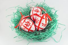 Nestandeggs. Whithe easter eggs with red decoration in green nest Stock Photography
