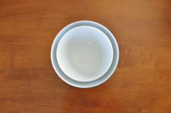 Nested White Bowls on Maple Table Royalty Free Stock Image