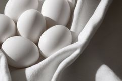Nesting purity. Low saturation Easter still life with pure white eggs wrapped softly in a white linen blanket Stock Images