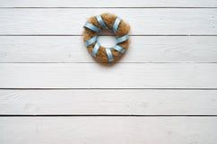 Nestkroon met blauw lint op witte houten planken rustieke achtergrond Royalty-vrije Stock Foto