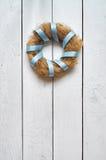 Nestkroon met blauw lint op witte houten planken rustieke achtergrond Royalty-vrije Stock Foto's