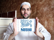Nestle logo. Logo of nestle company on samsung tablet holded by muslim man. Nestlé is the world`s leading nutrition, health and wellness company Stock Image