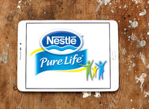 Nestle pure life logo. Logo of nestle pure life  mineral water on samsung tablet on wooden background Stock Photos
