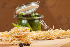 Nests of dry pasta and cucumbers. Nests of dry pasta on wooden table Royalty Free Stock Photography